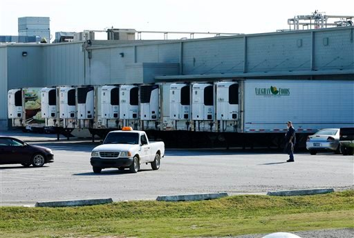 Trucks are parked in a parking lot at Vaughn Foods in Moore, Okla., Friday, Sept. 26, 2014, the site of an incident where a man beheaded a woman with a knife and was attacking another worker when he was shot and wounded by a company official, on Thursday.