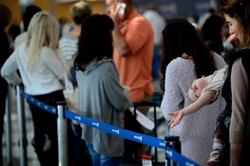 Ann Walden and her 15 month-old daughter Delphine wait in-line after their flight to Baton Rouge was delayed at O'Hare International Airport in Chicago, Friday, Sept. 26, 2014.
