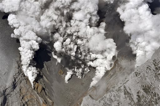 Dense fumes are spewed out from several spots on the slope of Mt. Ontake as the volcano erupts in central Japan Saturday, Sept. 27, 2014.