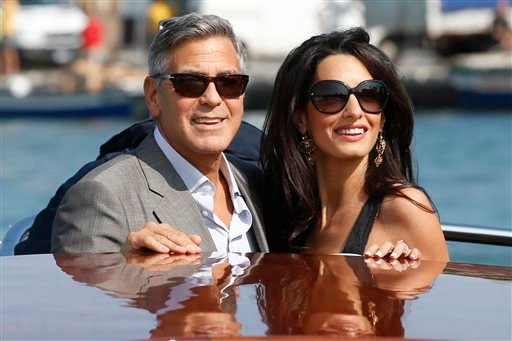 George Clooney, left, and Amal Alamuddin arrive in Venice, Italy, Friday, Sept. 26, 2014. Clooney, 53, and Alamuddin, 36, are expected to get married this weekend in Venice, one of the world's most romantic settings. (AP Photo/Luca Bruno)