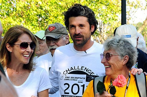 In this Oct. 8, 2011 file photo, actor Patrick Dempsey, center, prepares to start the Survivor Walk with his mother, Amanda, right, and Amgen Breakaway from Cancer Award winner Laura Davis in Lewiston, Maine, on the first day of the Dempsey Challenge.