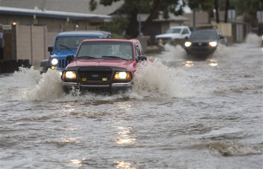 Vehicles drive through the flood prone area of 39th Avenue between Peoria Avenue and Cactus Road during a storm in Phoenix on Saturday, Sept. 27, 2014.