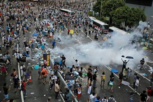 Riot police use tear gas against protesters after thousands of people blocked a main road at the financial central district in Hong Kong, Sunday, Sept. 28, 2014.