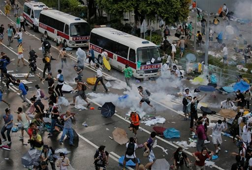 Protesters walk through tear gas used by riot police against protesters after thousands of people blocked a main road at the financial central district in Hong Kong, Sunday, Sept. 28, 2014.