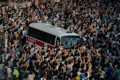 A police car is blocked by protesters after thousands of people block a main road to the financial central district outside the government headquarters in Hong Kong, Sunday, Sept. 28, 2014.