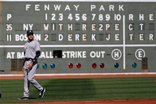 New York Yankees' Derek Jeter walks on the field in front of a message to him on the Green Monster scoreboard at Fenway Park, prior to the Yankees' baseball game against the Boston Red Sox, Sunday, Sept. 28, 2014, in Boston.