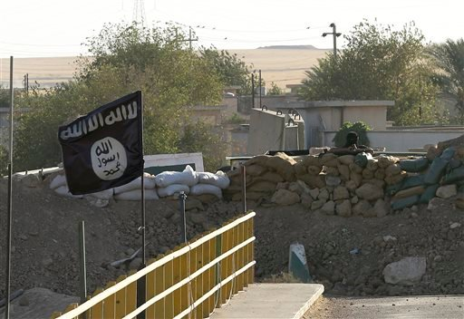 A black flag used by the Islamic State group flutters over their combat positions on the front line with Kurdish Peshmerga fighters at the Mullah Abdullah Bridge, located between Irbil and Kirkuk, 290 kilometers (180 miles) north of Baghdad, Iraq.