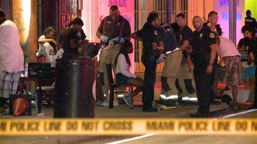 In this image taken from video, emergency personnel tend to the wounded outside The Spot, a nightclub in Miami, early Sunday, Sept. 28, 2014.