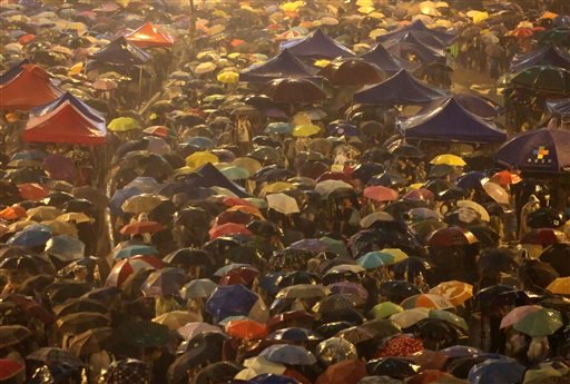 Pro-democracy protesters hold umbrellas under heavy rain in a main street near the government headquarters in Hong Kong late Tuesday, Sept. 30, 2014.