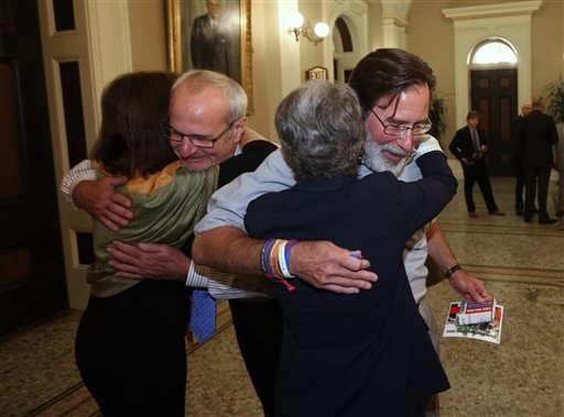 Aug. 27, 2014 file photo: Richard Martinez, right, whose son, Christopher Ross Michaels-Martinez was killed in a shooting spree in Isle Vista last May, hugs State Sen. (AP Photo/Rich Pedroncelli,file)