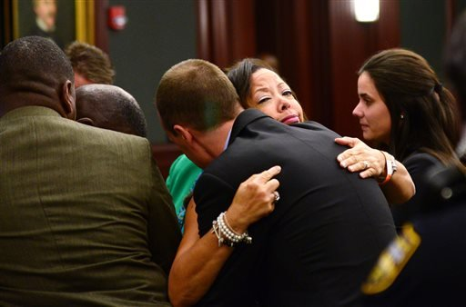 Lucia McBath, mother of Jordan Davis, hugs Det. Mark Musser of the Jacksonville Sheriff's Office, after the verdict in Michael Dunn's retrial, at the Duval County Courthouse in Jacksonville, Fla., Wednesday, Oct. 1, 2014. (AP)