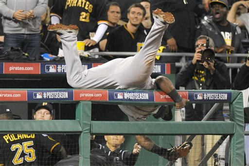 Giants third baseman Pablo Sandoval flips over the dugout railing after making a catch on a fly ball by Pirates' Andrew McCutchen in the seventh inning of the NL wild-card playoff baseball game Oct. 1, 2014, in Pittsburgh. (AP Photo/Don Wright)