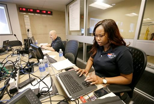 Dallas Emergency Management specialist Bridgette Smith, front and Greg Guthrie manage their stations as they work with other branches of city government in the Office of Emergency Management Oct. 1, 2014. (AP Photo/Tony Gutierrez)