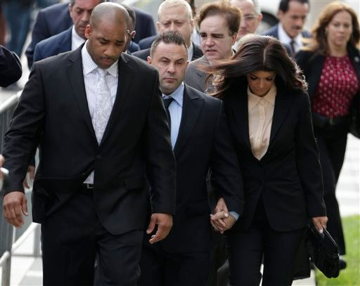 """""""The Real Housewives of New Jersey"""" stars Giuseppe """"Joe"""" Giudice, 43, center, and his wife, Teresa Giudice, 41, right, walk toward Martin Luther King, Jr. Courthouse before a court appearance, Thursday, Oct. 2, 2014, in Newark, N.J. (AP)"""