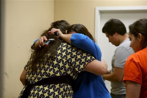 Unidentified relatives and friends of Bell Gardens mayor Daniel Crespo, grieve inside the city's police station in Bell Gardens, Calif., Tuesday, Sept. 30, 2014. (AP)
