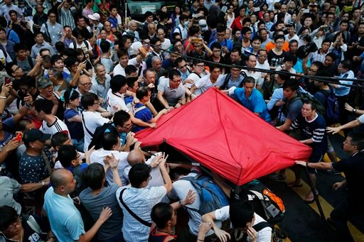 Residents and pro-Beijing supporters tear down a pro-democracy activist tent in Kowloon's crowded Mong Kok district, Friday, Oct. 3, 2014 in Hong Kong.