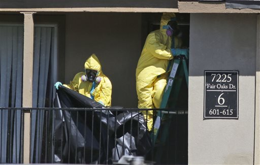 Hazardous material cleaners prepare to hang black plastic outside the apartment in Dallas, Friday, Oct. 3, 2014, where Thomas Eric Duncan, the Ebola patient who traveled from Liberia to Dallas stayed last week.