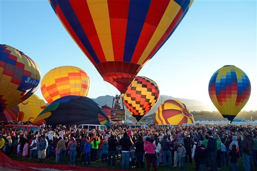 A balloon lifts off over the crowd in the early morning during the annual Albuquerque International Balloon Fiesta in Albuquerque, N.M. Saturday, Oct. 4, 2014.