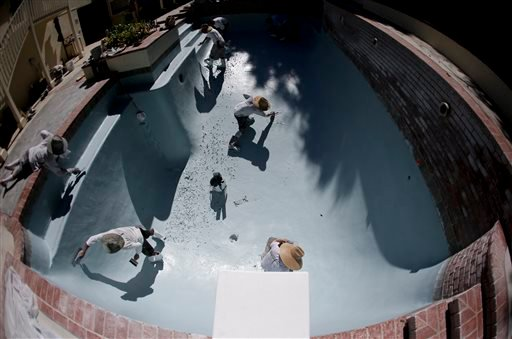 Workers replace the plaster in a swimming pool in Santa Ana, Calif. on Wednesday, Sept. 24, 2014.