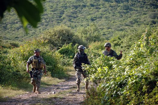 Mexican marines guard the road that leads to the site where an alleged clandestine mass grave was found near the city of Iguala, Mexico, Saturday, Oct. 4, 2014.