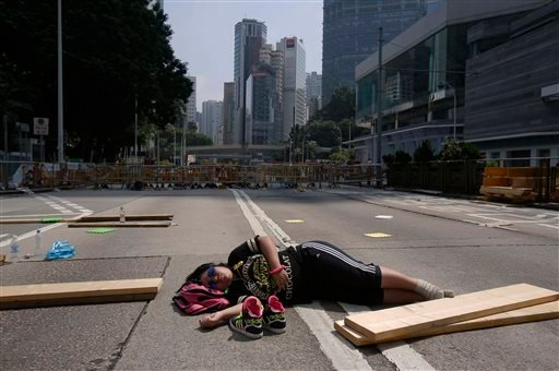 A lone pro-democracy student protester sleeps in the middle of an occupied road in Hong Kong, Sunday, Oct. 5, 2014.