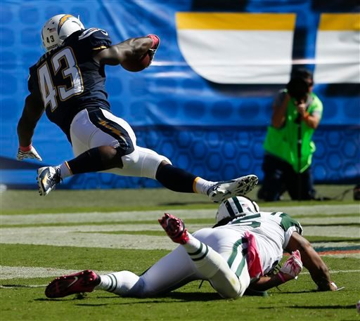 San Diego Chargers running back Branden Oliver scores over New York Jets free safety Calvin Pryor during the first half of an NFL football game, Sunday, Oct. 5, 2014, in San Diego. (AP Photo/Lenny Ignelzi)