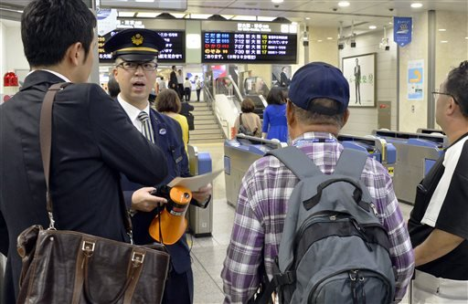 An employee of Japan Railways speaks to passengers as train schedule go haywire at Nagoya Station in Nagoya, central Japan Monday, Oct. 6, 2014.