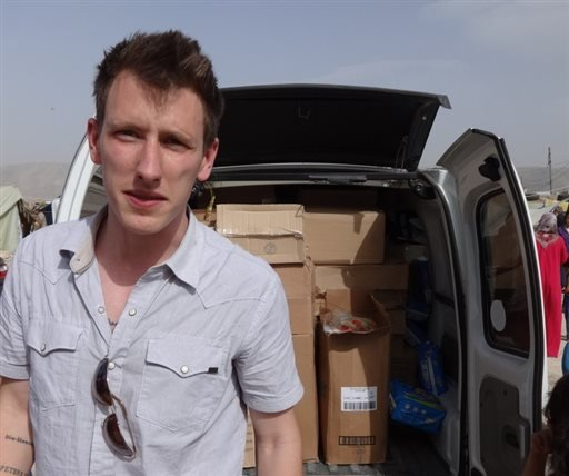 This undated photo provided by Kassig Family shows Peter Kassig standing in front of a truck filled with supplies for Syrian refugees.