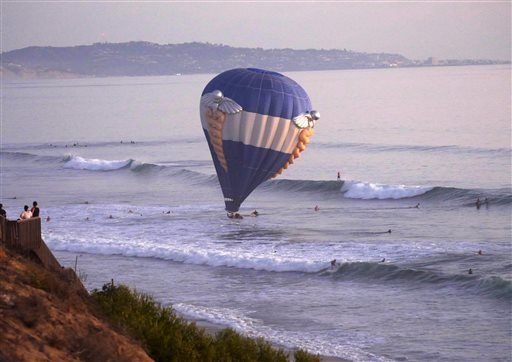 In this Sunday, Oct. 5, 2014 photo provided by Jenny Parsons, a hot air balloon dips into the ocean in Cardiff-by-the-Sea, a beach community in Encinitas, Calif. (AP Photo/Jenny Parsons)