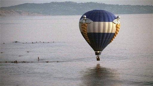 In this Sunday, Oct. 5, 2014 photo provided by Jenny Parsons, a hot air balloon dips close to the ocean as it is pulled in by surfers in Cardiff-by-the-Sea, a beach community in Encinitas, Calif. (AP Photo/Jenny Parsons)