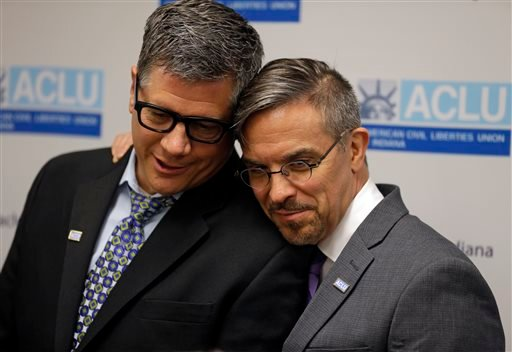 Rob MacPherson, right, and his husband Steven Stolen, hug during a news conference at the ACLU in Indianapolis, Monday, Oct. 6, 2014. (AP Photo/Michael Conroy)