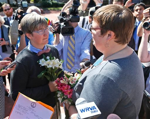 Nicole Pries, left, and Lindsey Oliver exchange vows Monday, Oct. 6, 2014, as the couple become one of the first same-sex couples in Virginia to be married, outside a Richmond Court building in Richmond, Va. (AP Photo/Steve Helber)