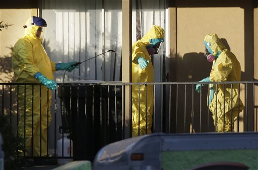 Hazardous material cleaners disinfectant their personal protective equipment after working in the apartment where Thomas Eric Duncan, the Ebola patient who traveled from Liberia to Dallas, stayed last week, Sunday, Oct. 5, 2014, in Dallas.