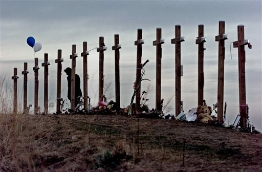 This April 28, 1999 file photo shows a woman standing among 15 crosses posted on a hill above Columbine High School in Littleton, Colo., in remembrance of the 15 people who died during a school shooting on April 20.