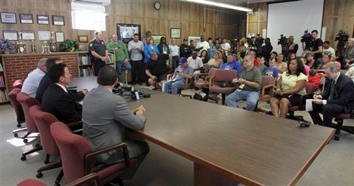 In this Friday, Oct. 3, 2014 photo, members of the Sayreville Board of Education, seated left, hold a press conference at the Selover School in South Amboy, N.J.