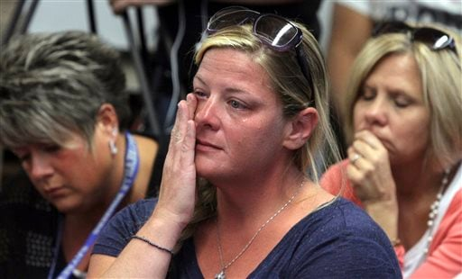 """In this Friday, Oct. 3, 2014 photograph, audience members react as members of the Sayreville Board of Education hold a news conference at the Selover School in South Amboy, N.J., to address a hazing incident that """"went too far""""."""