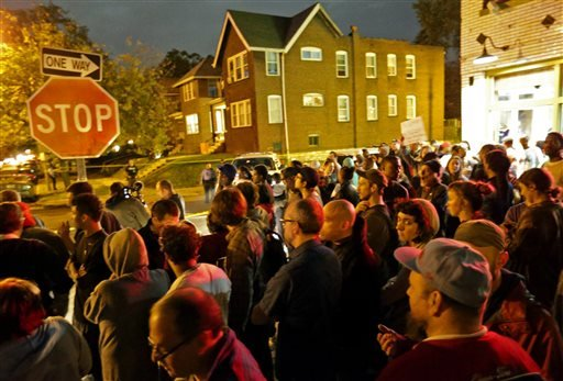 A crowd gathers near the scene in the 4100 block of Shaw Boulevard where a man was fatally shot by an off-duty St. Louis police officer on Wednesday, Oct. 8, 2014. St. Louis Police Lt. Col. (AP Photo/St. Louis Post-Dispatch, David Carson)