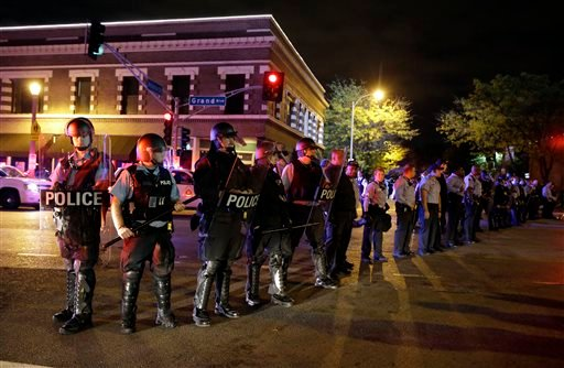 Police wearing riot gear form a line to contain protesters Thursday, Oct. 9, 2014, a day after Vonderrit D. Myers was shot and killed by white, off-duty St. Louis police officer in St. Louis.