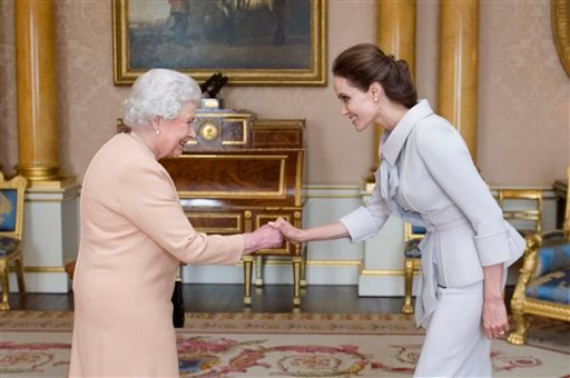 U.S actress Angelina Jolie, right, is presented with the Insignia of an Honorary Dame Grand Cross of the Most Distinguished Order of St Michael and St George by Britain's Queen Elizabeth II at Buckingham Palace, London, Friday, Oct. 10, 2014.