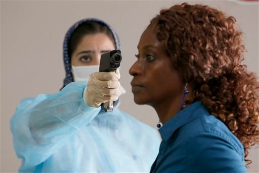 A Moroccan health worker uses a thermometer to screen a passenger at the arrivals hall of the Mohammed V airport in Casablanca, on Thursday, Oct 9, 2014.