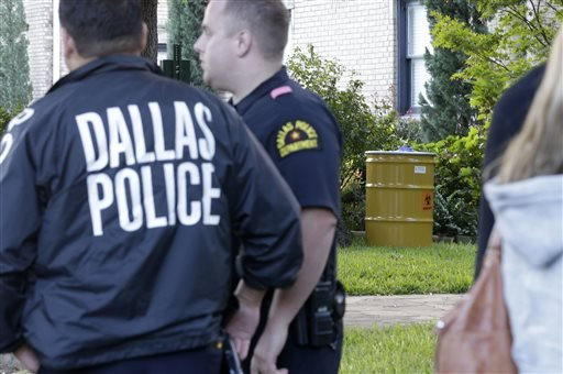 Police stand guard outside the apartment of a hospital worker and a yellow barrel, left, that holds hazardous materials, Sunday, Oct. 12, 2014, in Dallas.