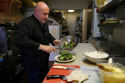 Chef Michele Massimo prepares a salad in the kitchen of his restaurant Botto Bistro Wednesday, Oct. 1, 2014, in Richmond, Calif.