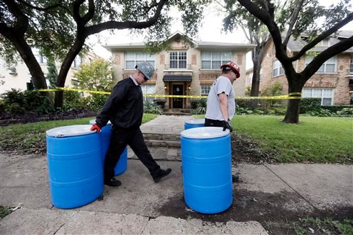 Protect Environmental workers move disposal barrels to a staging area outside the apartment of a healthcare worker who treated Ebola patient Thomas Eric Duncan and tested positive for the disease, Monday, Oct. 13, 2014, in Dallas. (AP Photo/Brandon Wade)