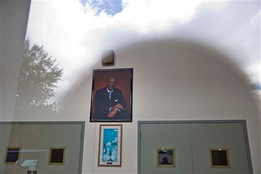 The sun and clouds are reflected off a glass on the entrance of the Shiloh Missionary Baptist Church where a portrait of pastor Juan D. McFarland hangs on the wall on Tuesday, Oct. 14, 2014, in Montgomery, Ala. (AP)