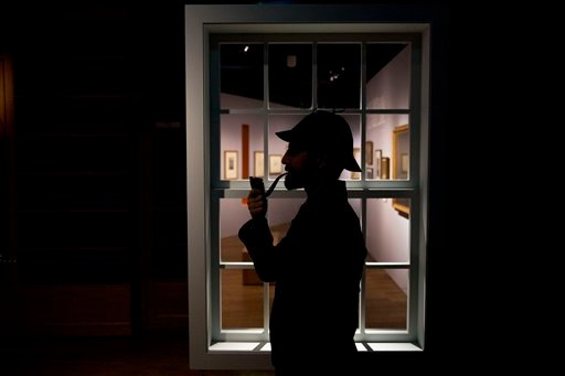 Curator Timothy Long is silhouetted as he poses for photographers with a Sherlock Holmes style pipe and deerstalker hat beside an internal window. (AP Photo/Matt Dunham)