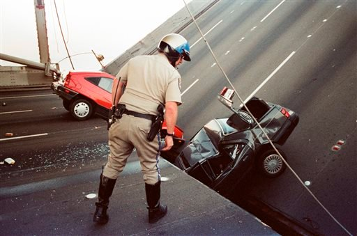 In this Oct. 17, 1989 file photo, a California Highway Patrol officer checks the damage to cars that fell when the upper deck of the Bay Bridge collapsed onto the lower deck after the Loma Prieta earthquake in San Francisco.