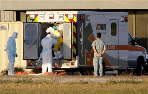 Medical staff in protective gear escort Nina Pham, exiting the ambulance, to a nearby aircraft at Love Field, Thursday, Oct. 16, 2014, in Dallas.