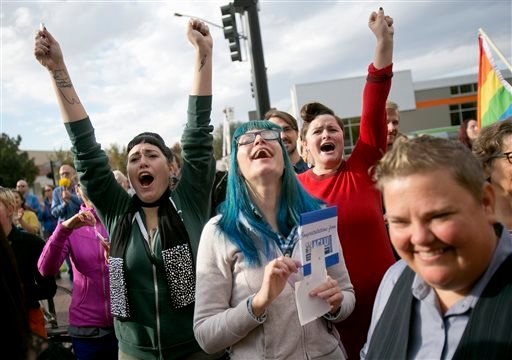 Well-wishers yell encouragement to same sex couples, including Karen McMillan, right, make their way out of the Ada County Courthouse after they received their marriage license, Wednesday, Oct. 15, 2014, in Boise, Idaho. (AP)