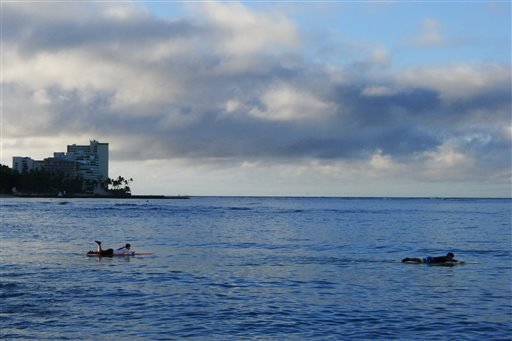 Surfers paddle out to catch waves, Friday, Oct. 17, 2014 near Waikiki Beach in Honolulu. Hurricane Ana remained far enough away from the Hawaiian islands to allow tourists to enjoy the mostly sunny weather. (AP Photo/Cathy Bussewitz)