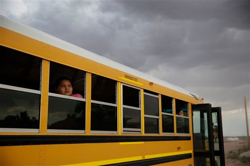 In this photo taken Sept. 25, 2014, fifth grader Jamika Salas looks out the window of a school bus after school at the Little Singer Community School in Birdsprings, Ariz. on the Navajo Nation.